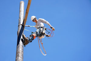 Student climbing pole at lineworker training facility